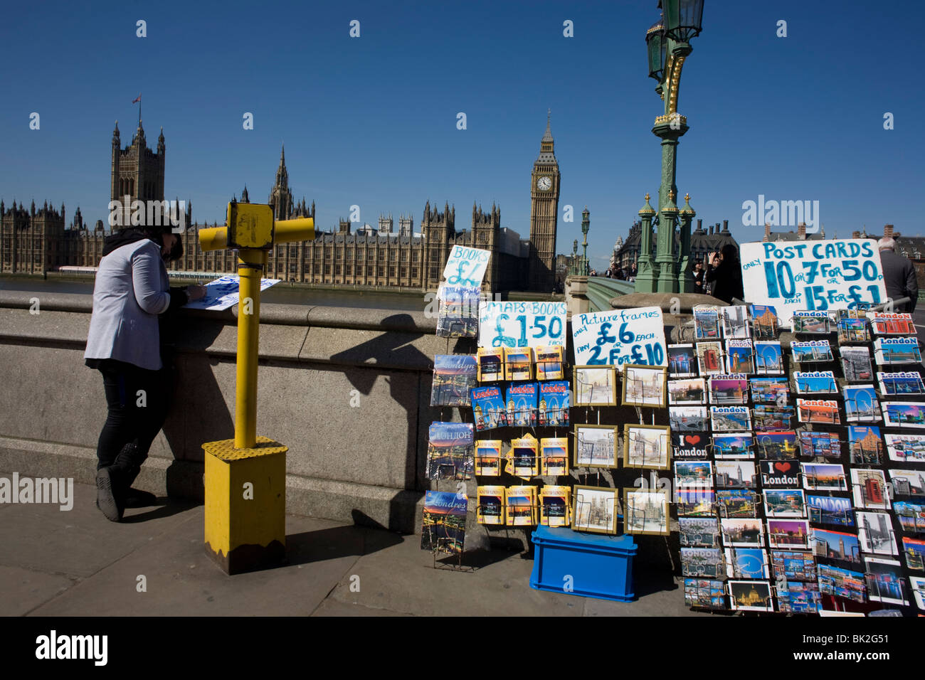 Big Ben amid the Gothic architecture of Britain's Houses of Parliament and tourist postcards displayed on the - Stock Image