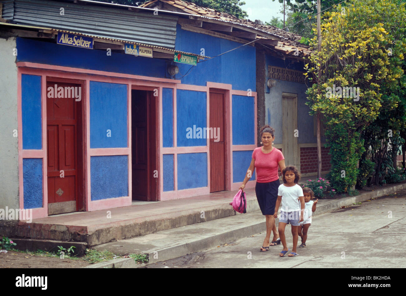 Woman and two young children walking down a street in Moyogalpa, Isla de Ometepe or Ometepe Island, Nicaragua Stock Photo