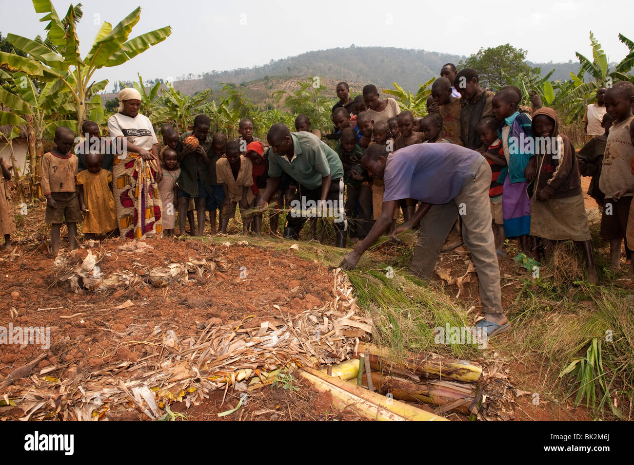 Farmer and local Aid worker building a keyhole garden whilst community watch on and learn. Rwanda. Stock Photo
