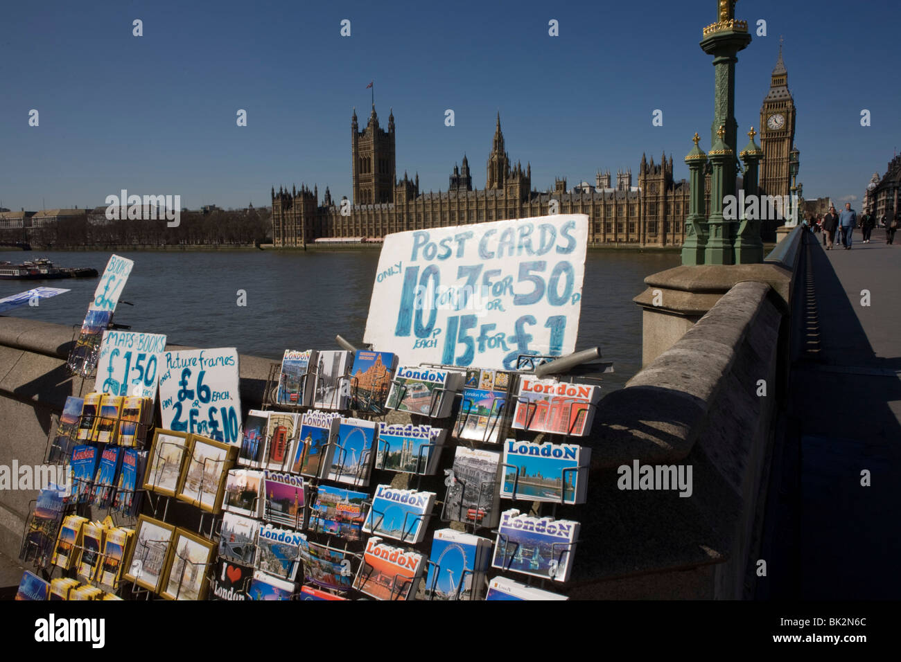 Elizabeth Tower amid the Gothic architecture of Britain's Houses of Parliament and tourist postcards displayed - Stock Image