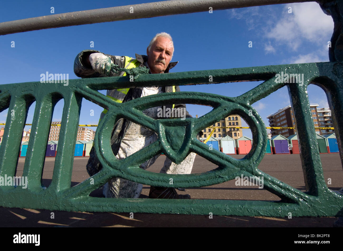 An older man painting the cast iron railings along the seafront promenade of Brighton and Hove - Stock Image