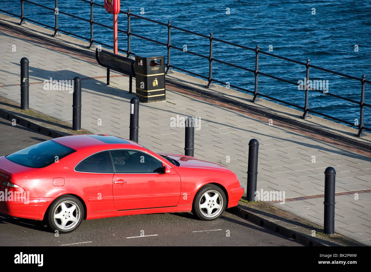 red car parked waterfront Barry UK - Stock Image