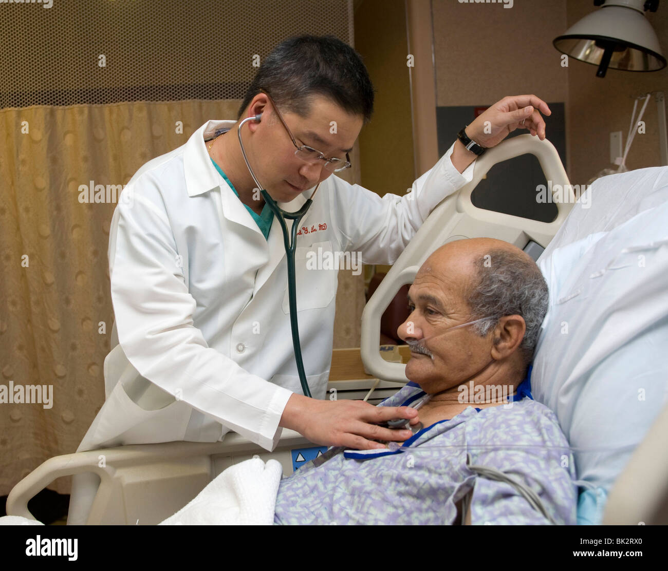 Surgeon examines heart patient as he recovers from surgery at a New York City hospital. - Stock Image