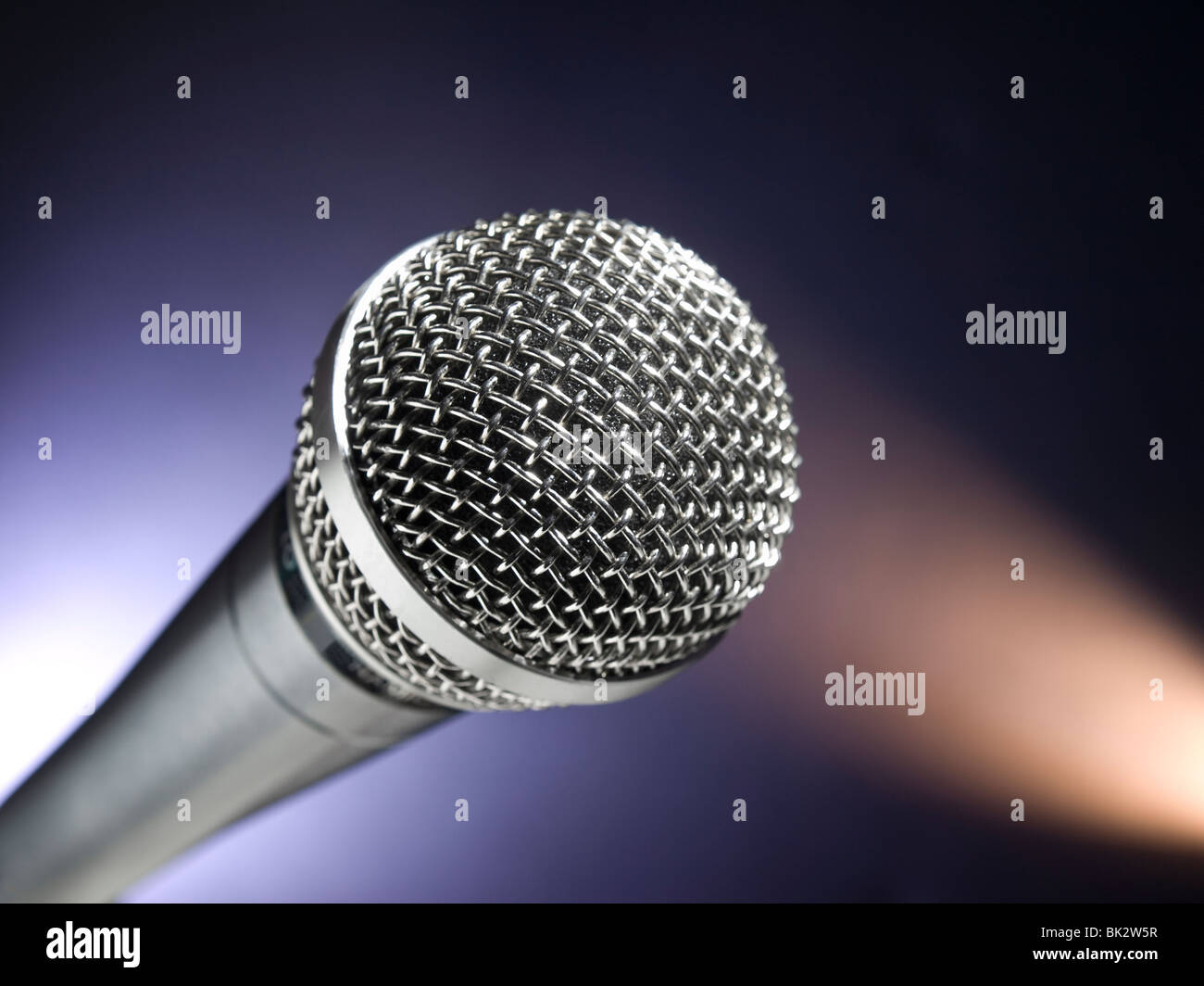 A dynamic microphone on stage. Color spot lights as background. - Stock Image