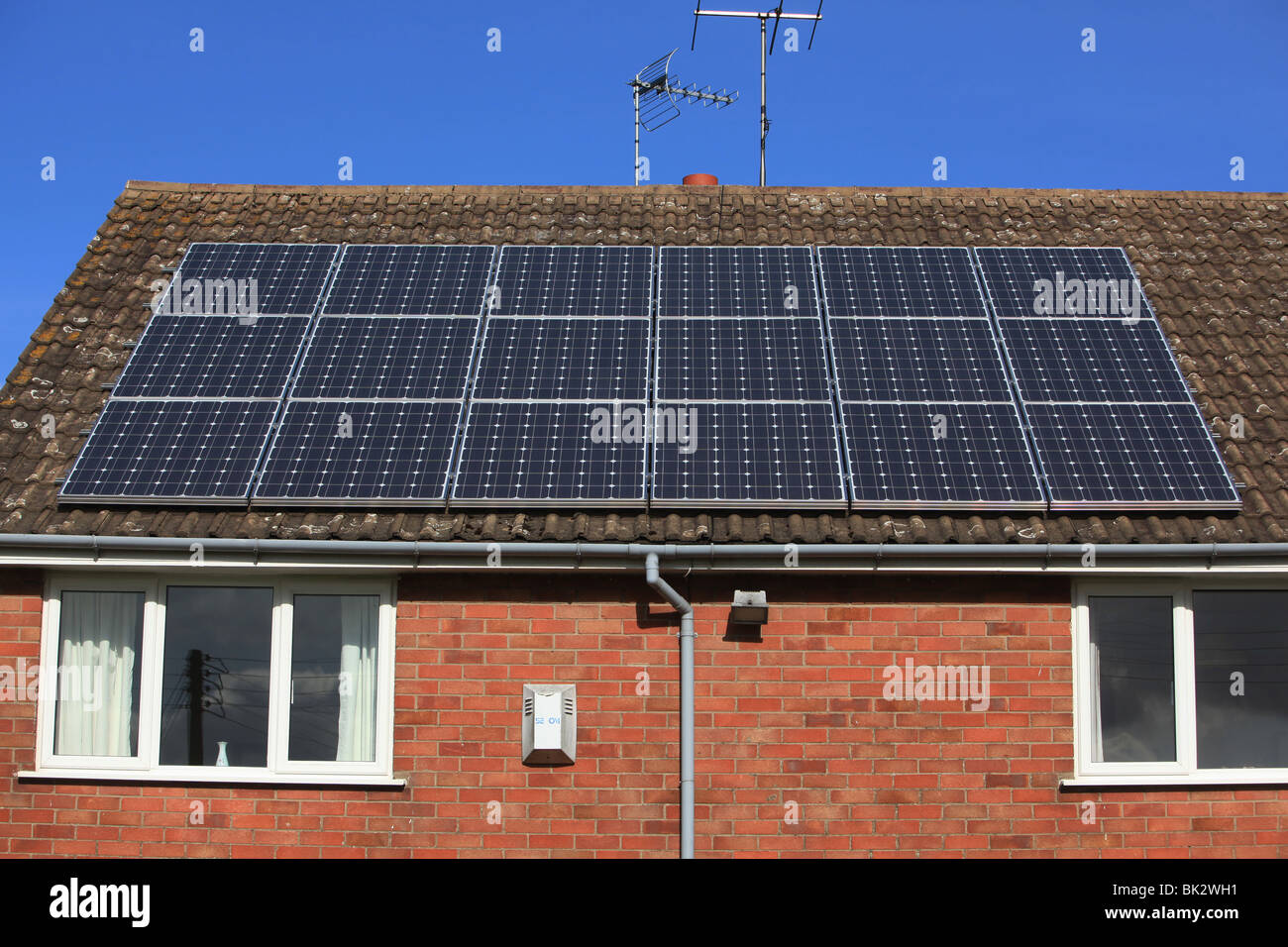 A UK residential house with new solar panel heating on its roof on a sunny clear blue sky day - Stock Image