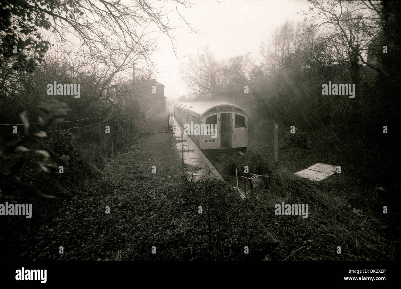 The end of the line for a London Underground tube train seen here sitting in a heavy rain storm at dis used Ongar Stock Photo