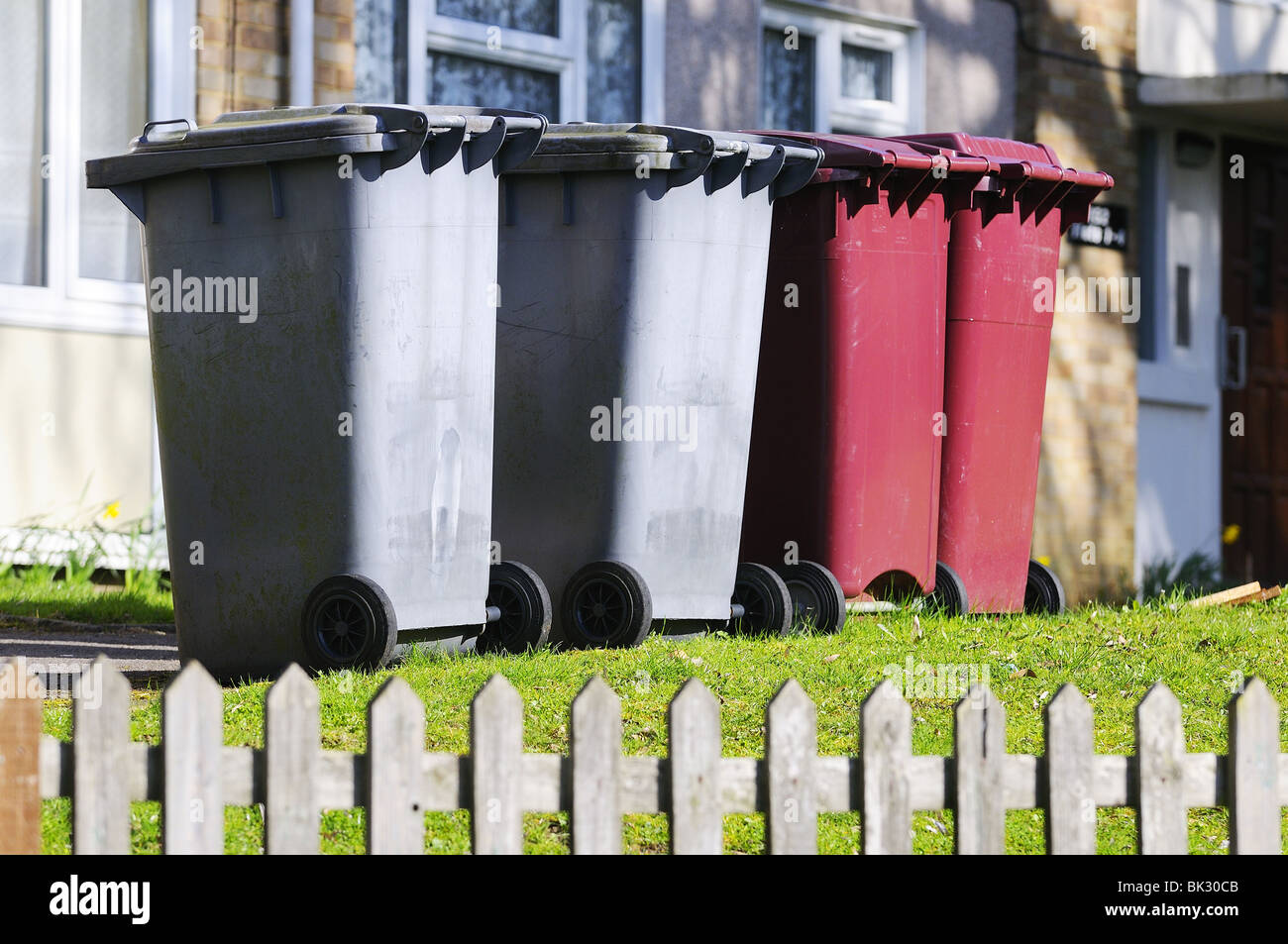 Domestic  rubbish 'wheelie  bins' waiting outside houses for refuse collectors, - Stock Image