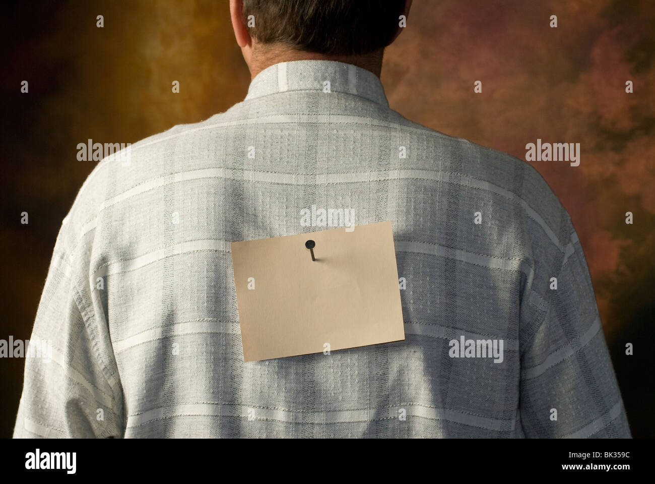 note nailed to man's back Stock Photo