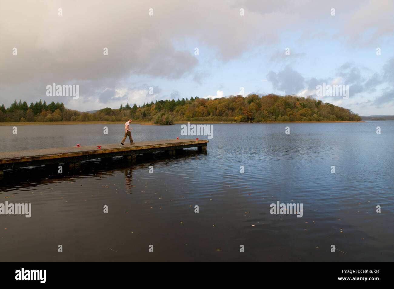 Man walks to the edge of the water on a jetty - Stock Image