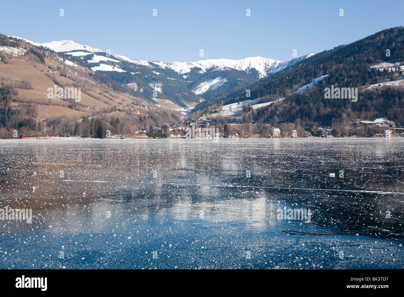 Frozen Zeller See lake with snow capped mountains reflected in ice in alpine resort. Zell am See, Austria, Europe - Stock Image