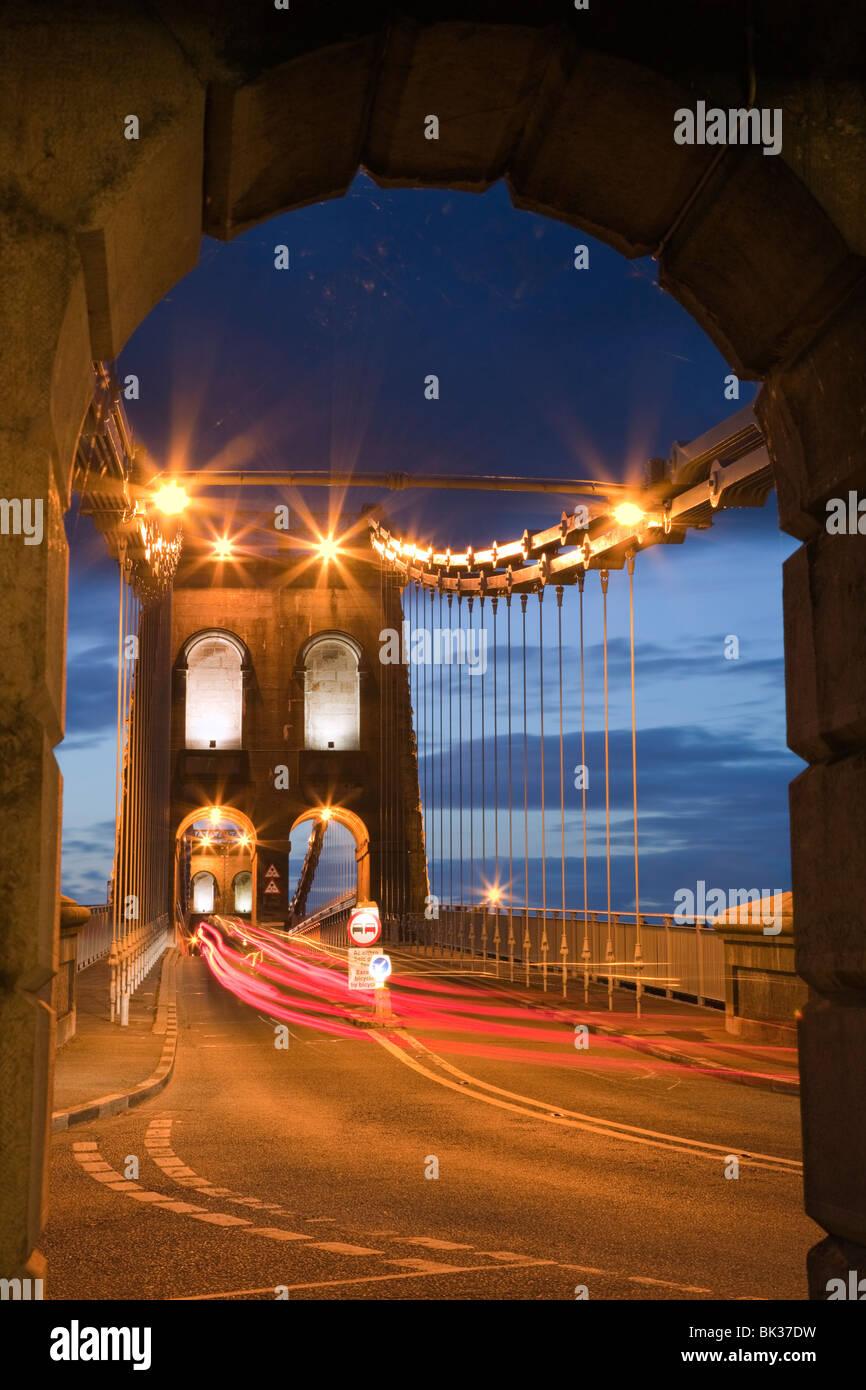 View along the A5 road at night across the Menai suspension bridge, by Thomas Telford in 1825, Bangor, Gwynedd, - Stock Image
