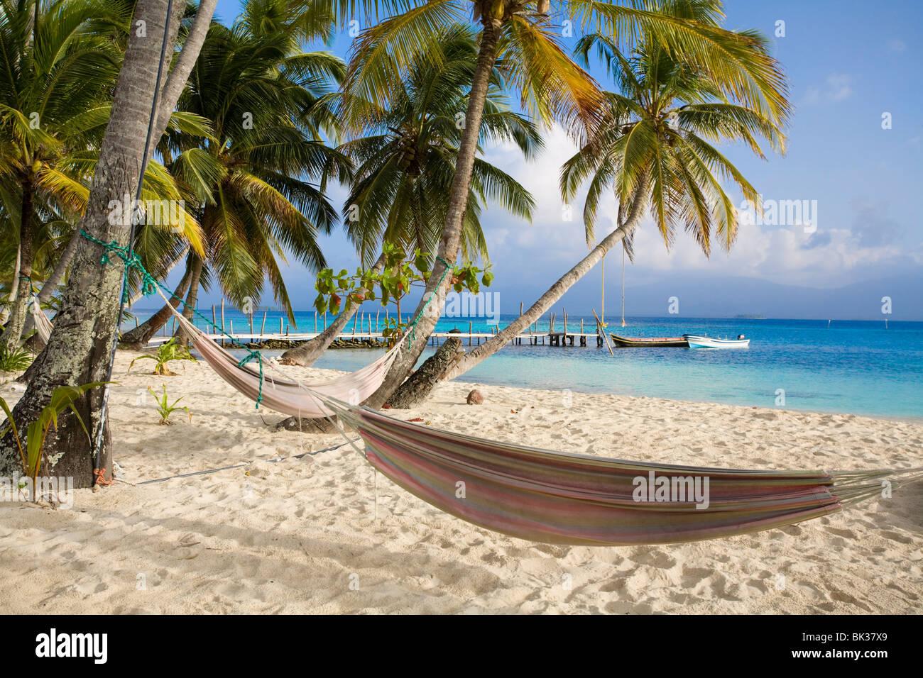 Hammocks hanging between palm trees, Kuanidup Grande, Comarca de Kuna Yala, San Blas Islands, Panama, Central America - Stock Image
