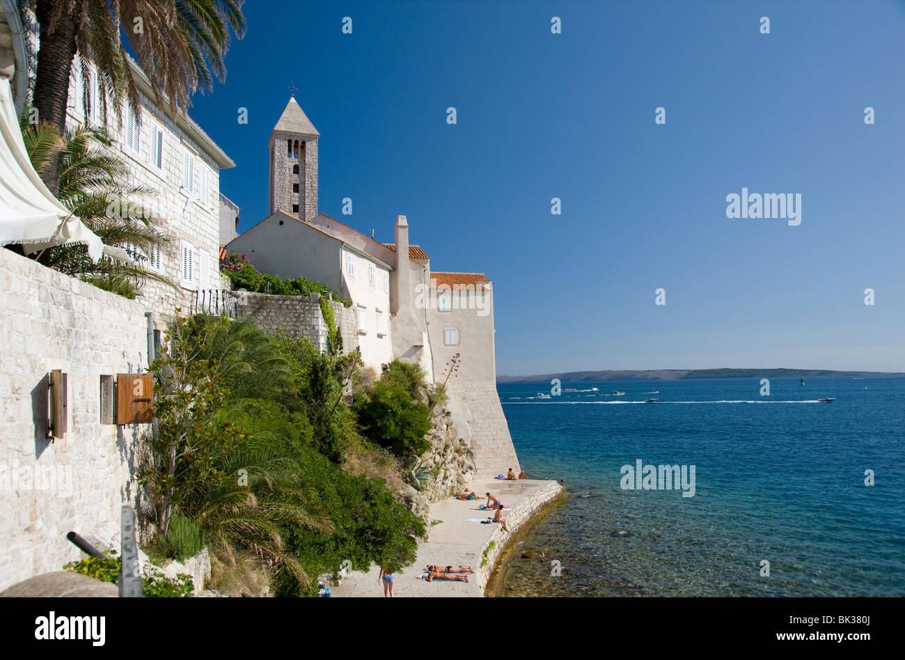 Swimmers and sunbathers on rock wall next to Rab Town, island of Rab, Kvarner region, Croatia, Europe - Stock Image