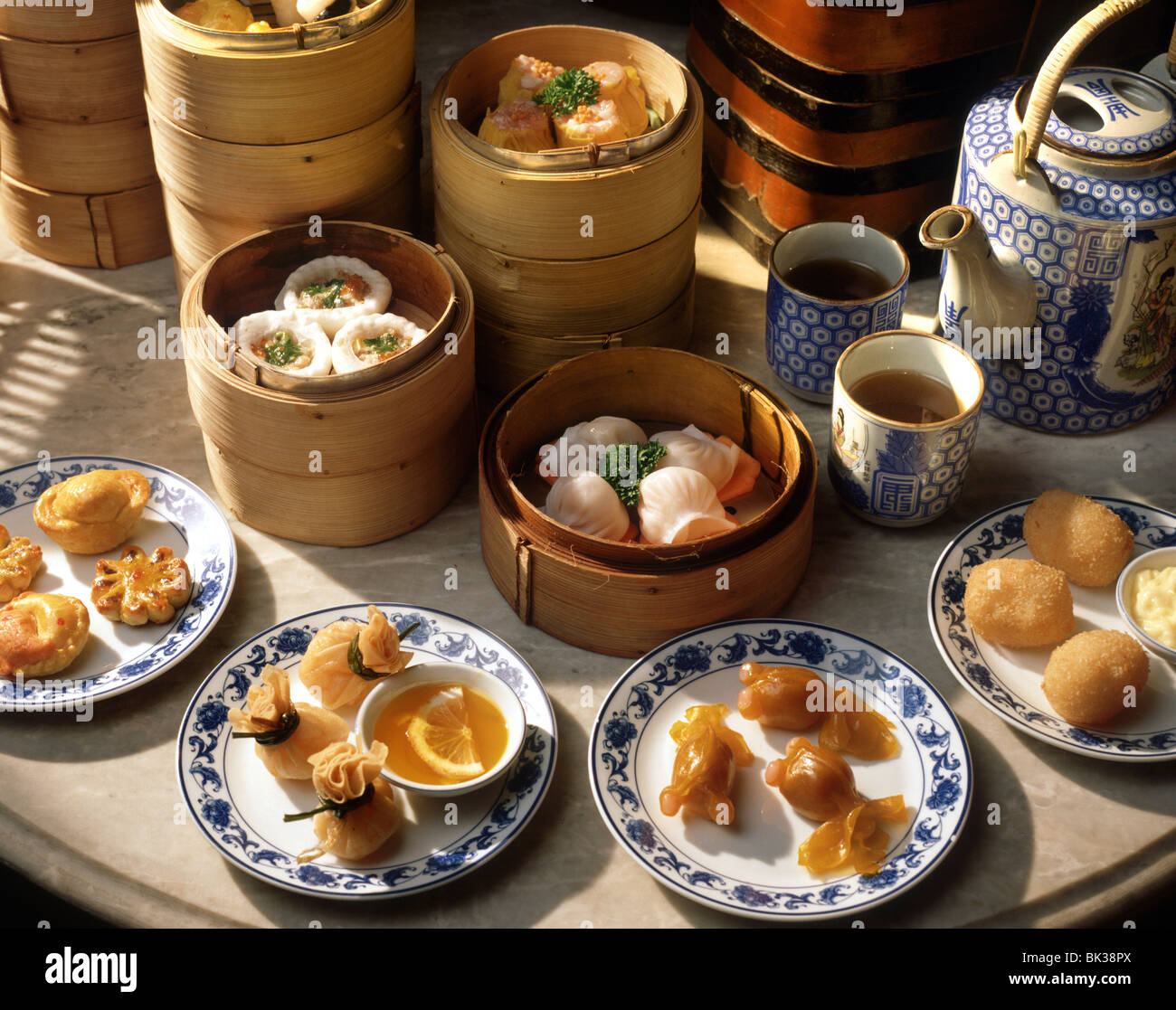 Steamers and plates of dim sum with tea, China, Asia - Stock Image