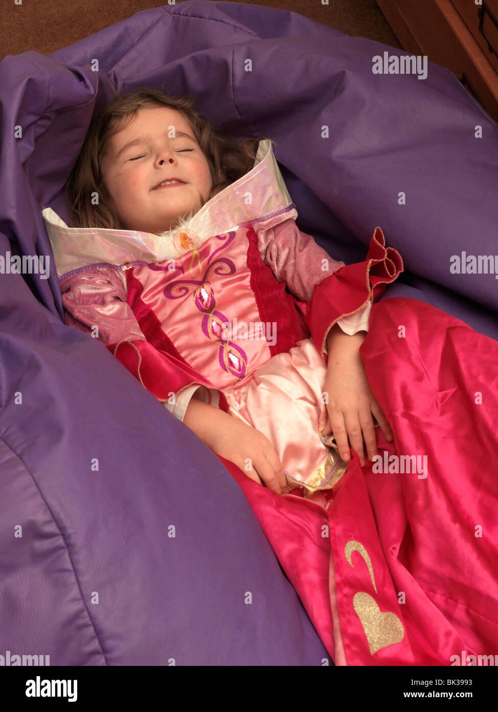 Young Girl Sleeping On Bean Bag In Princess Costume England Stock Photo