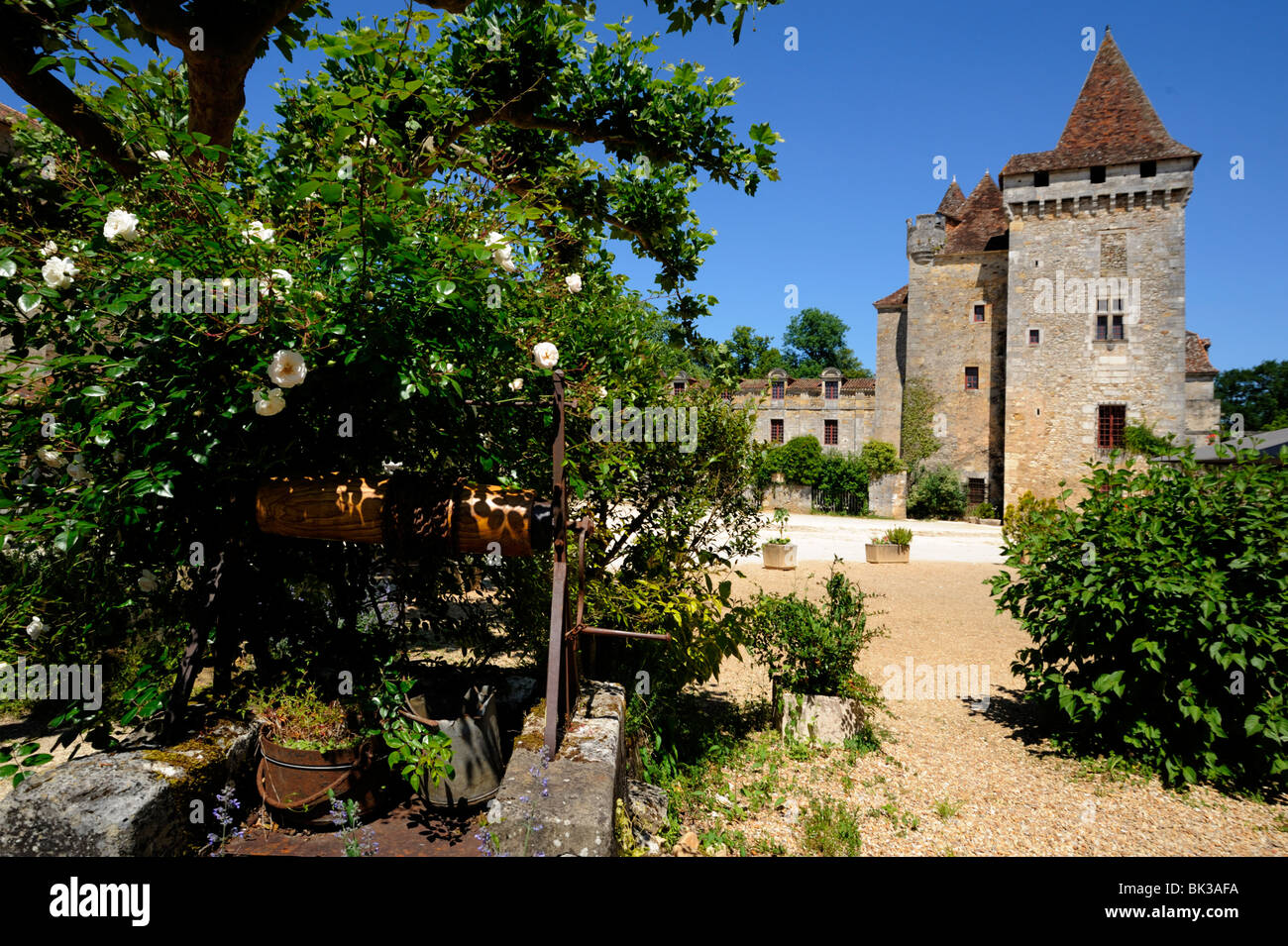 Old well with Le Chateau de la Marthonie in the background, St. Jean de Cole, Dordogne, France, Europe Stock Photo