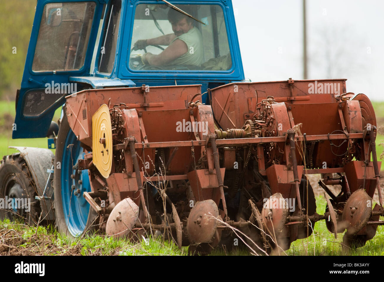 The tractor with a plough ploughs a meadow. - Stock Image