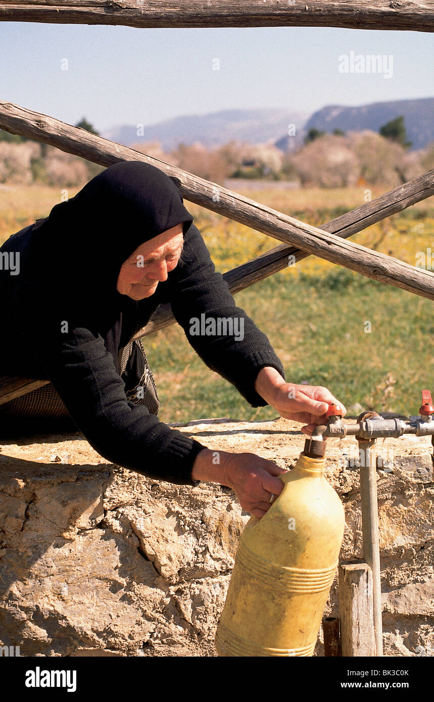 Woman filling a water container from a public waterline, Greece - Stock Image