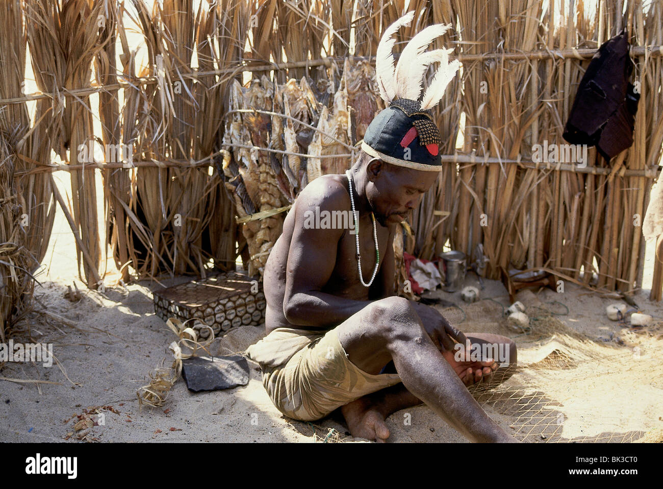 Kenyan near Lake Turkana, repairing a fishing net, Kenya - Stock Image