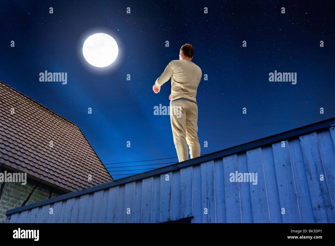Sleepwalker strolling on a flat roof under a full moon - Stock Image