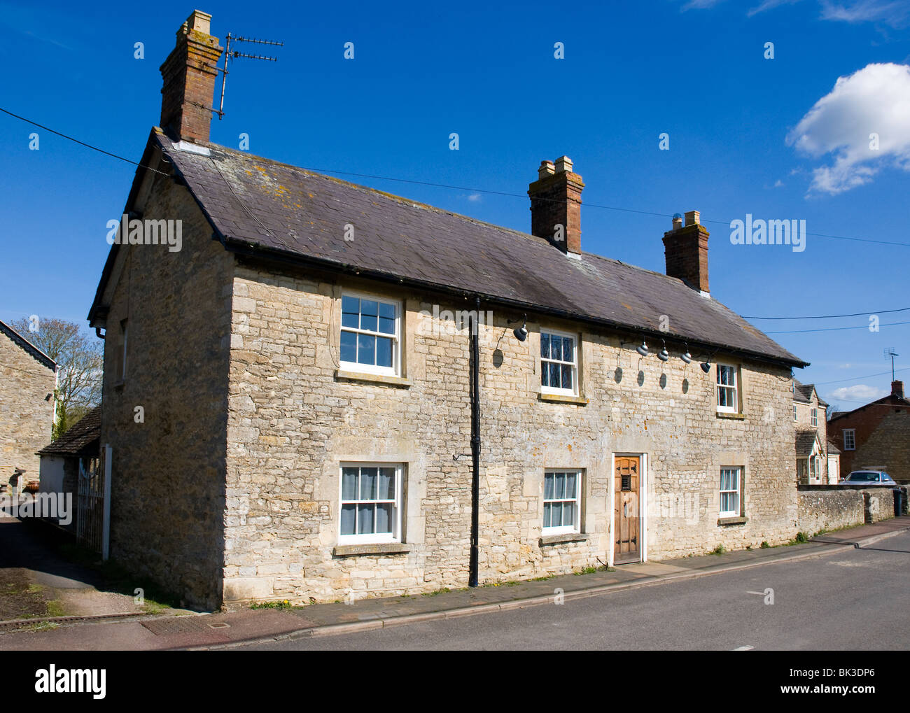 A closed down village pub in the cotswolds.  Pub lights still visible on the wall - Stock Image