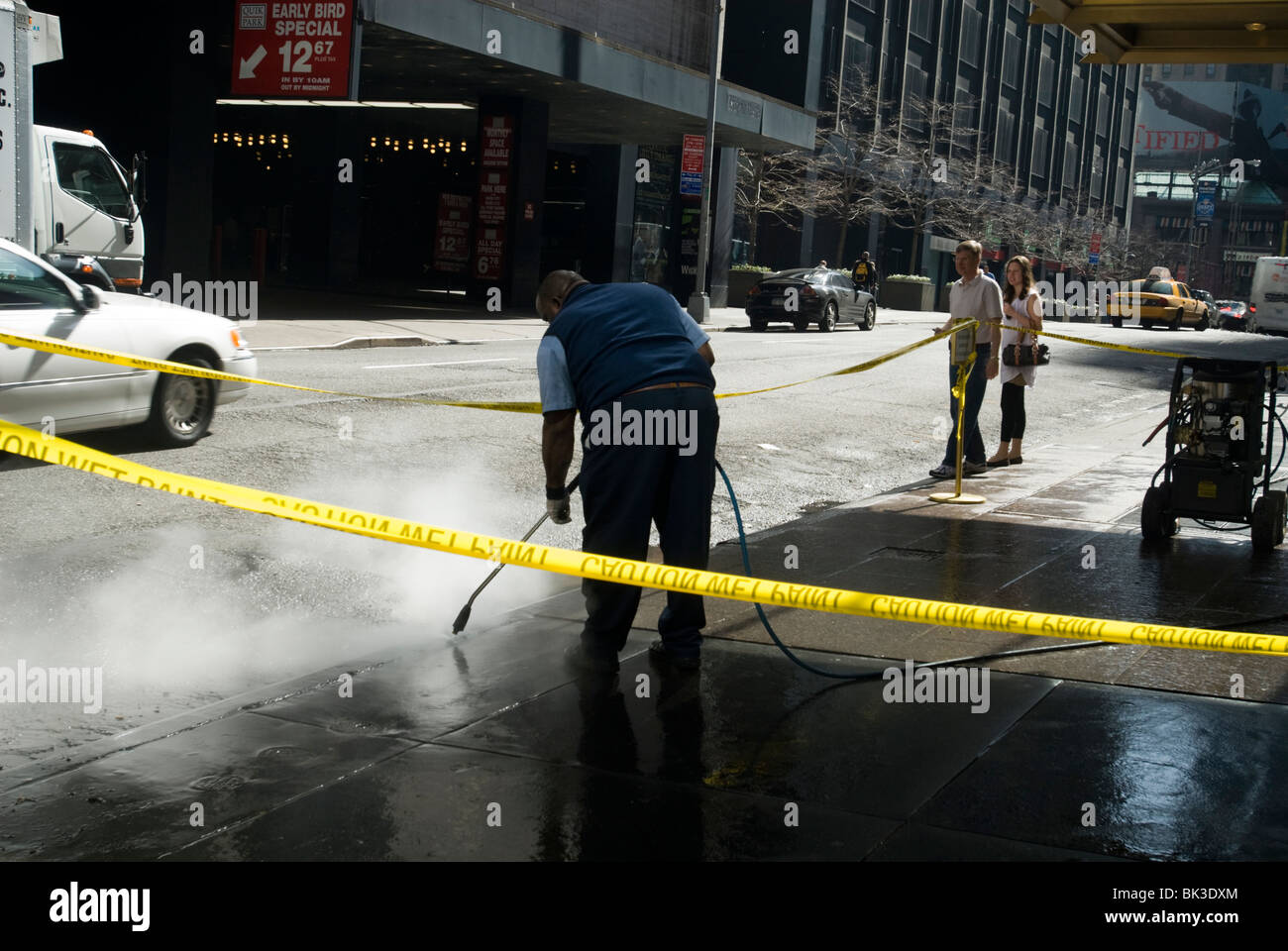 A worker uses a high pressure water hose to clean a sidewalk in New York - Stock Image