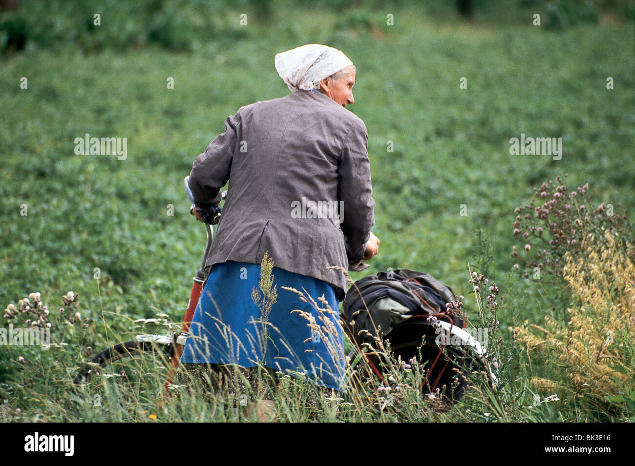 Woman with head scarf and bicycle, Poland - Stock Image