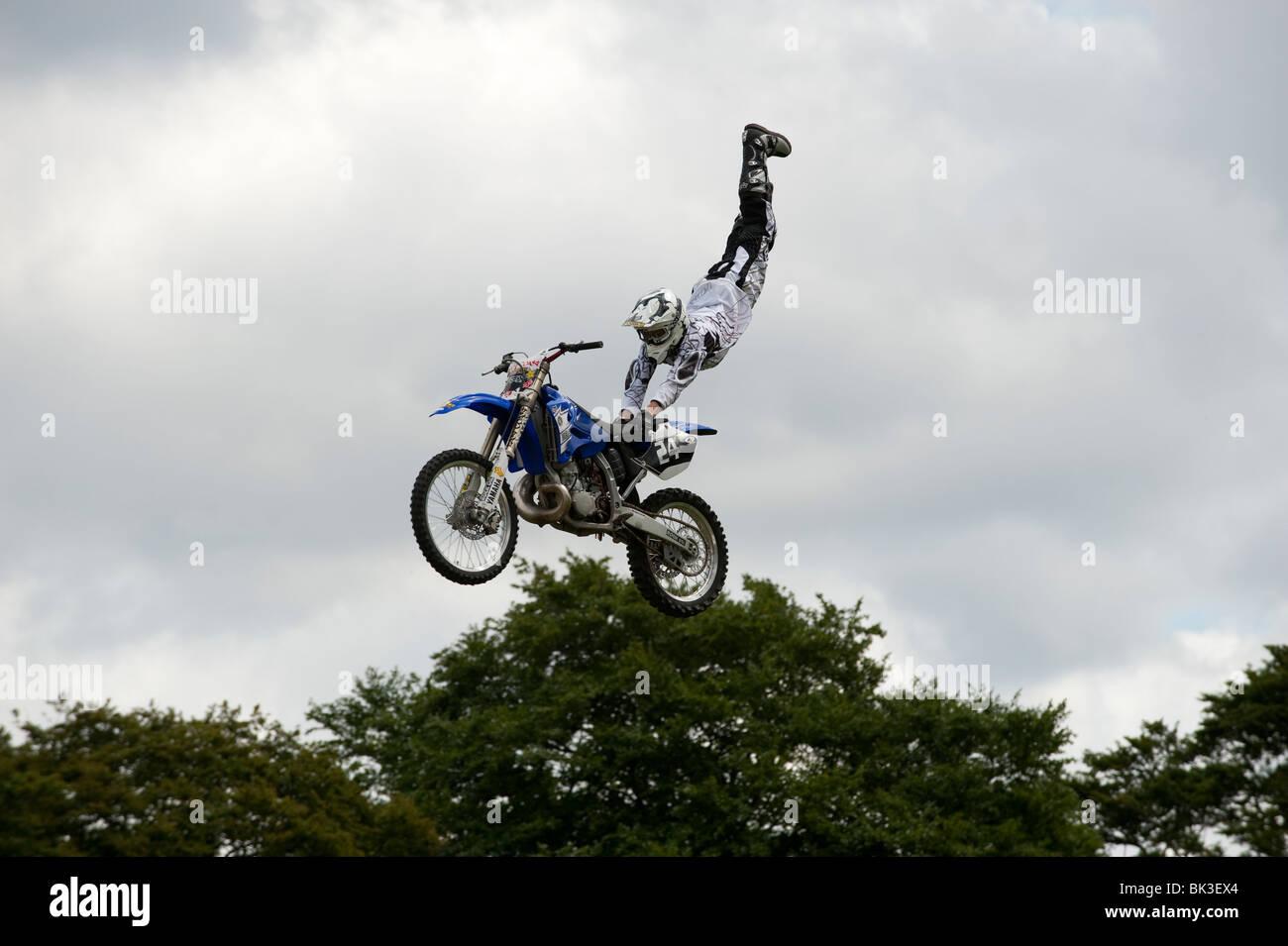 Acrobatic motorbike stunt man in air - Stock Image
