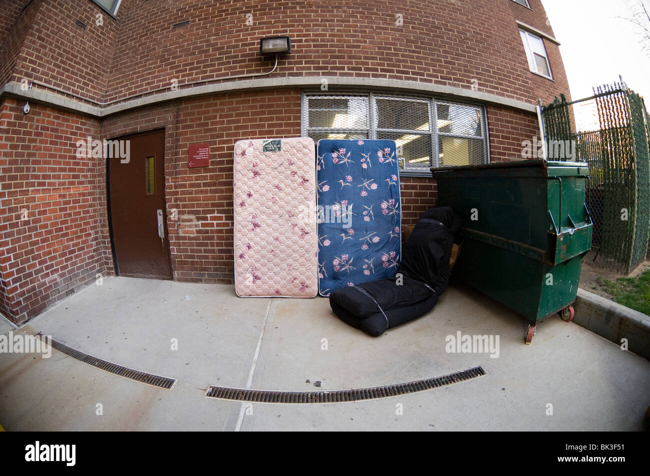Mattresses wait for bulk pick-up in the trash area of an apartment building in New York - Stock Image