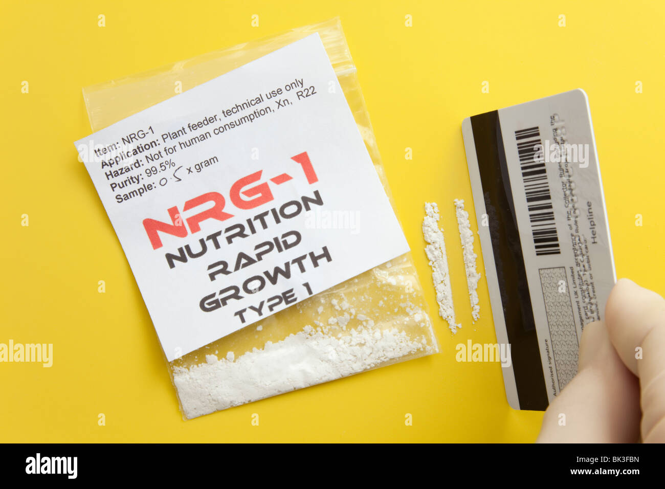 Britain, UK, Europe. Person making drug lines by a packet of NRG-1 plant food, popular as a legal high in UK. - Stock Image
