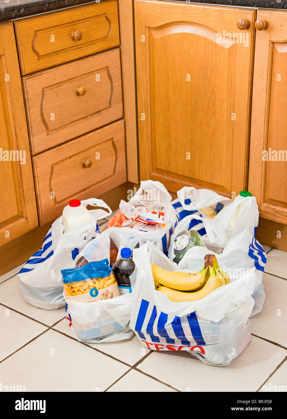 Grocery bags / carrier bags / shopping bags on a kitchen floor UK - Stock Image