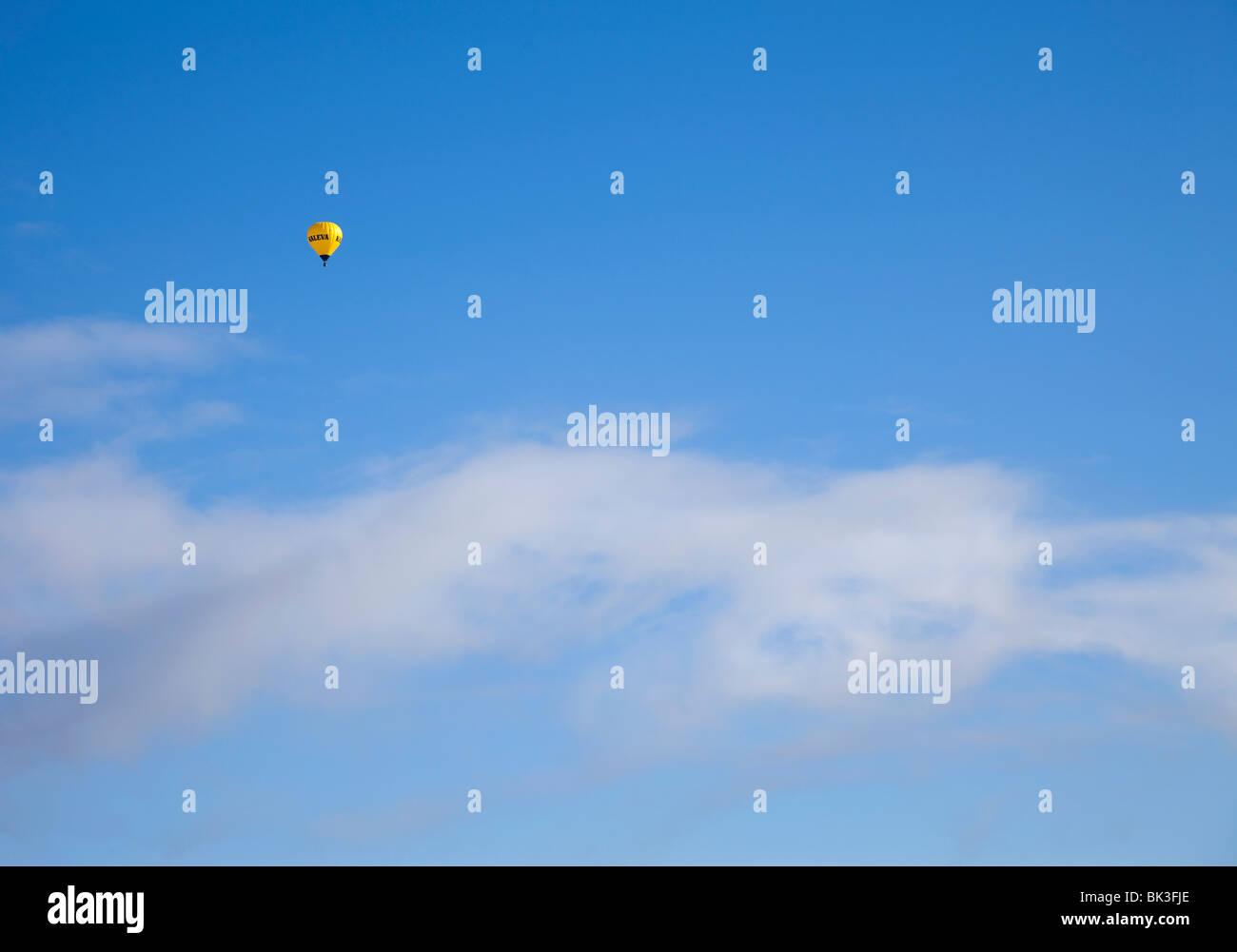 Tiny yellow hot air balloon on blue sky Stock Photo