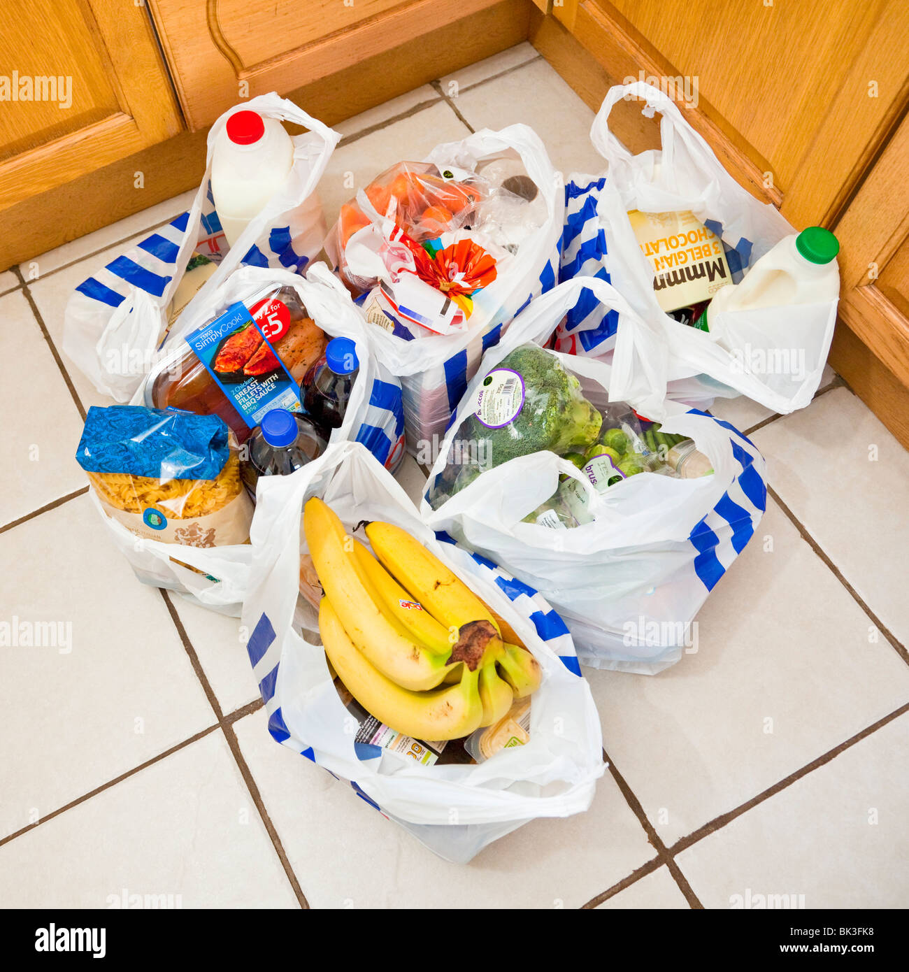 Grocery bags, carrier bags, shopping bags on a kitchen floor, England, UK - Stock Image