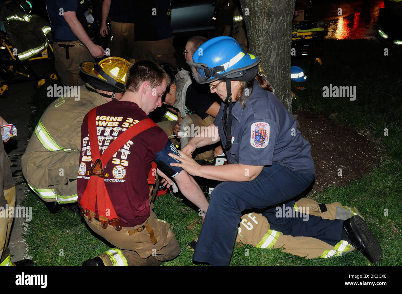 Medic takes blood pressure of a firefighter who had just  fiought an intense fire in Greenbelt, Maryland - Stock Image