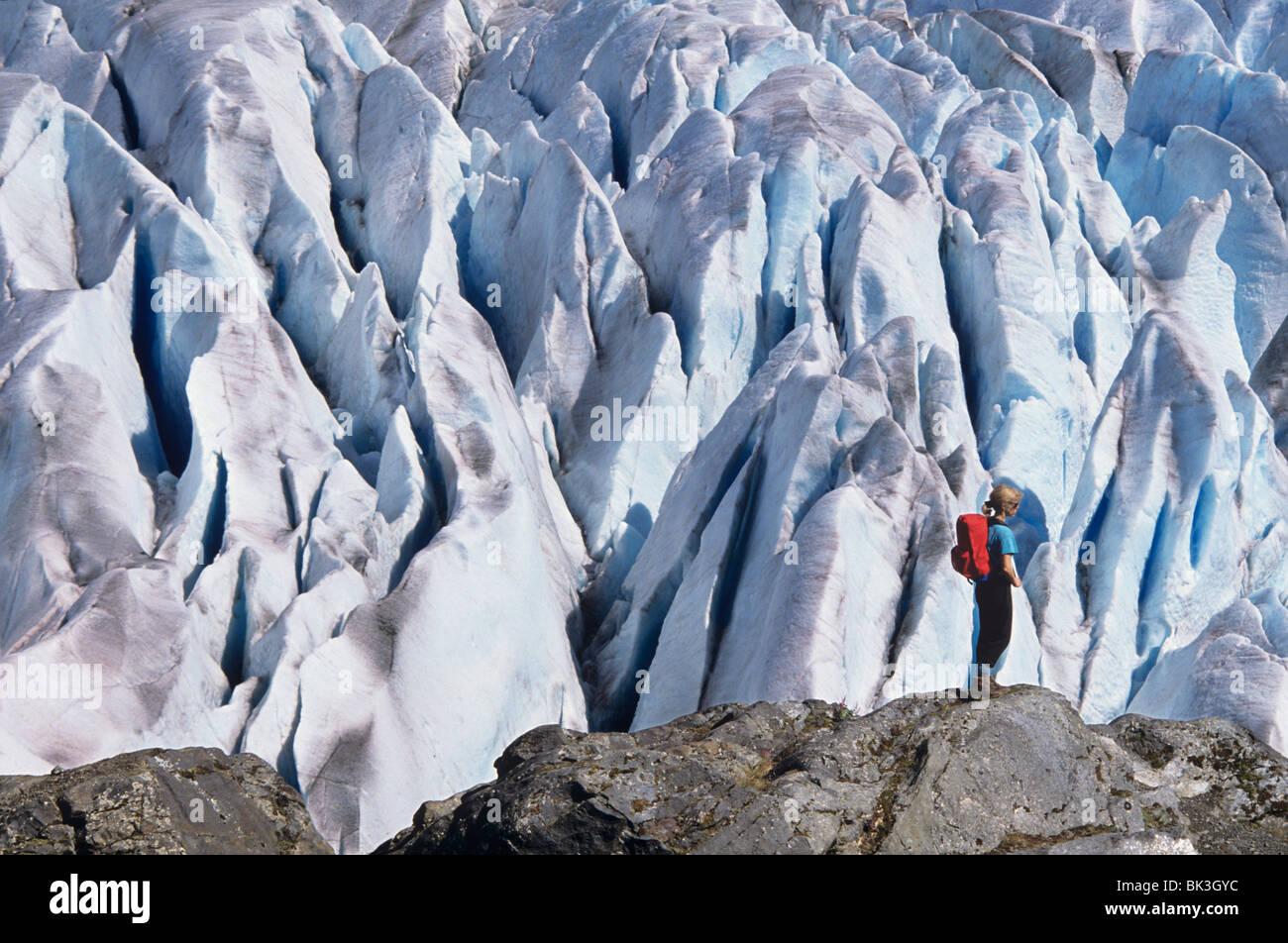 Woman standing on rock overlooking seracs on Mendenhall Glacier outside town of Juneau, Alaska. Stock Photo