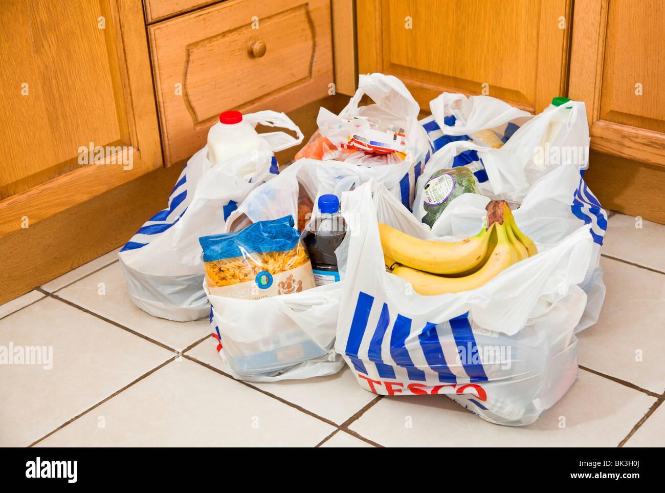 Tesco carrier bags full of shopping on a kitchen floor UK - Stock Image
