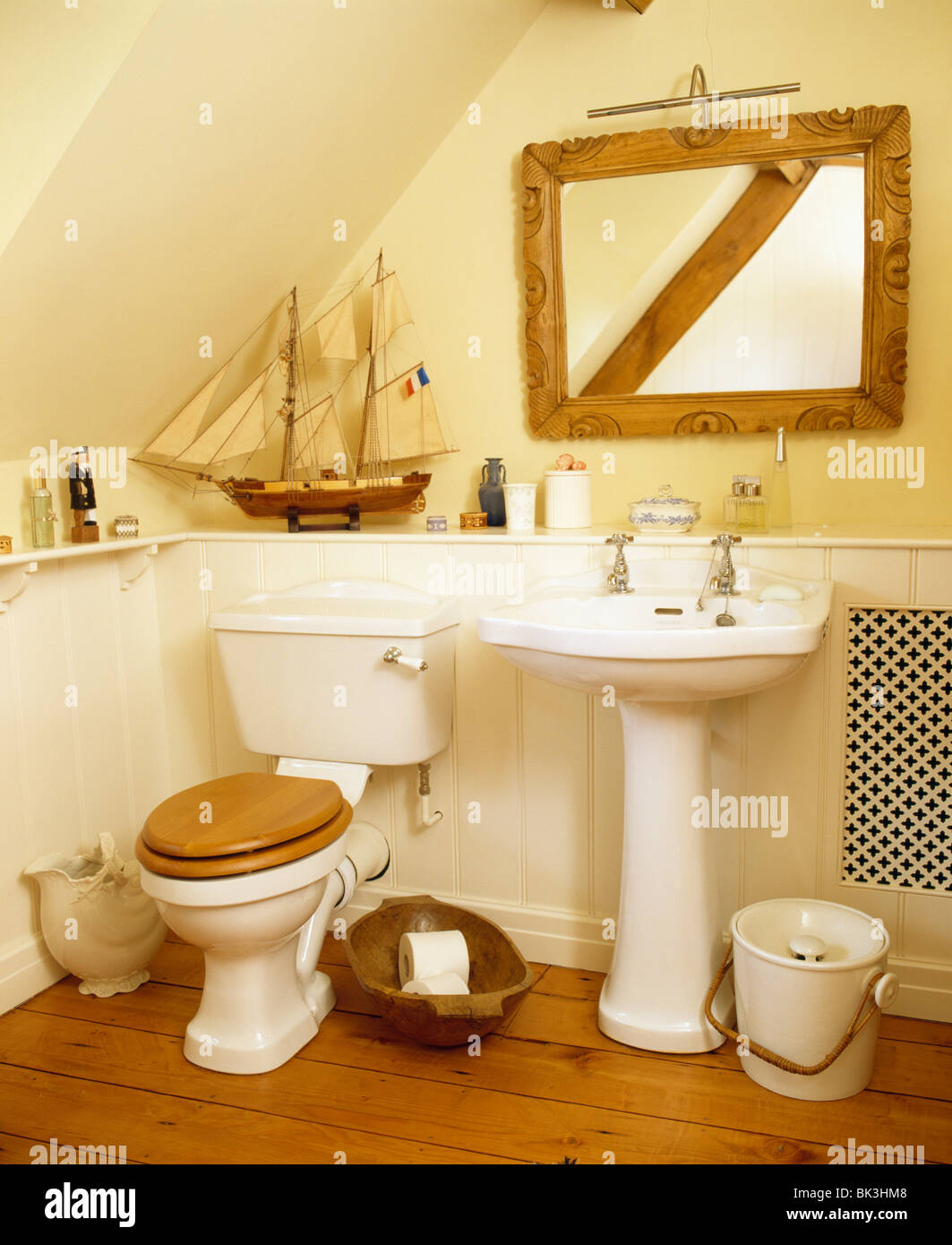 Wooden-framed mirror above white pedestal basin in cottage bathroom ...