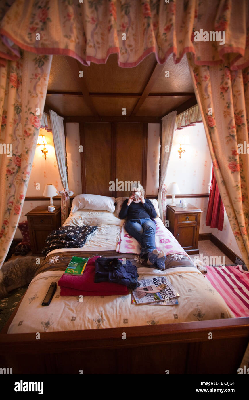 Lady laying on a four poster bed, having a drink out of a cup. lights on, clothes and newspaper on bed - Stock Image