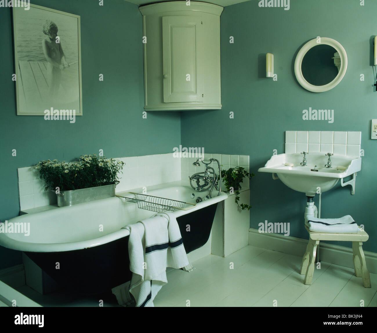 Roll-top bath and white corner wall-cupboard in gray-blue bathroom ...