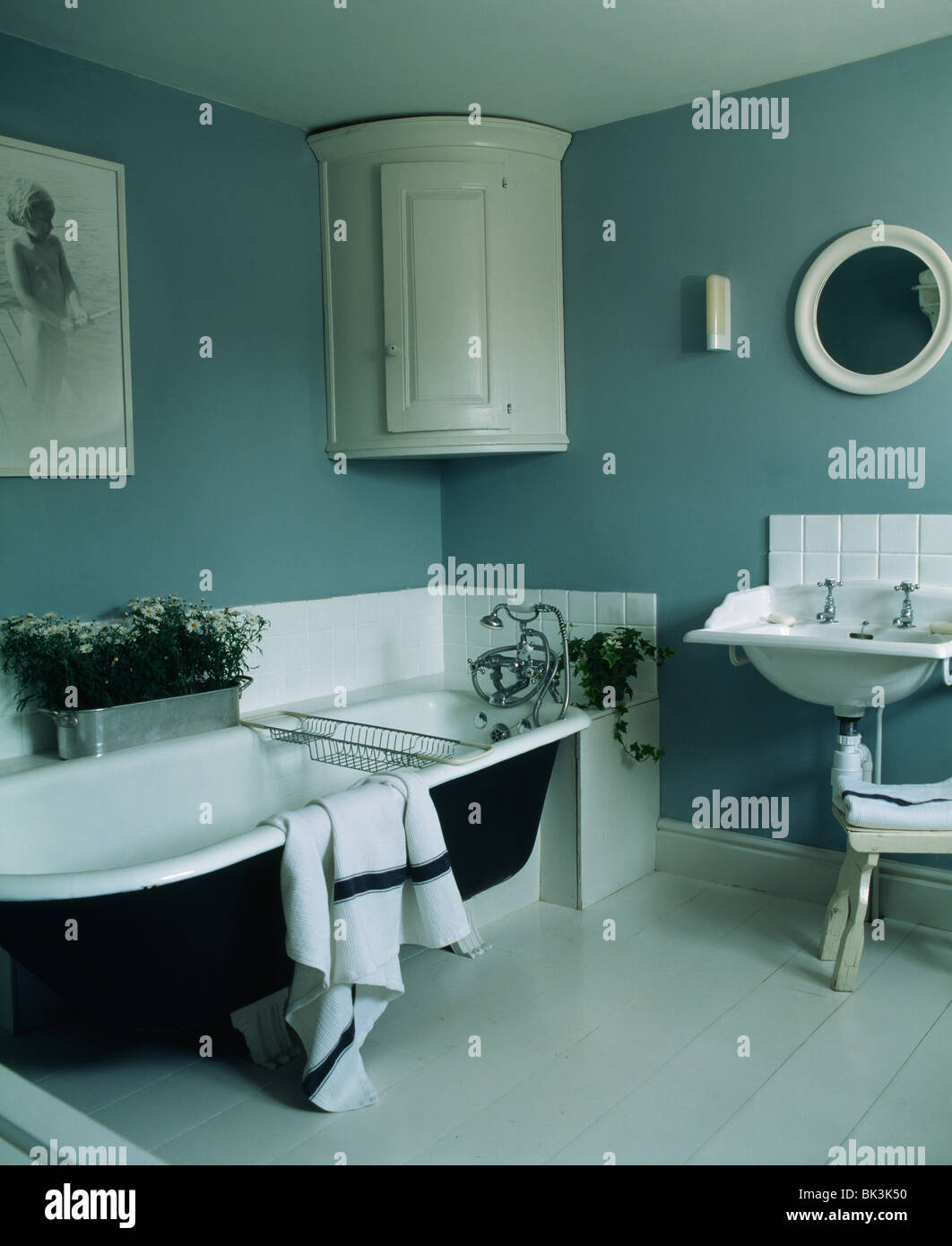 Roll-top bath in blue-gray country bathroom with white corner Stock ...