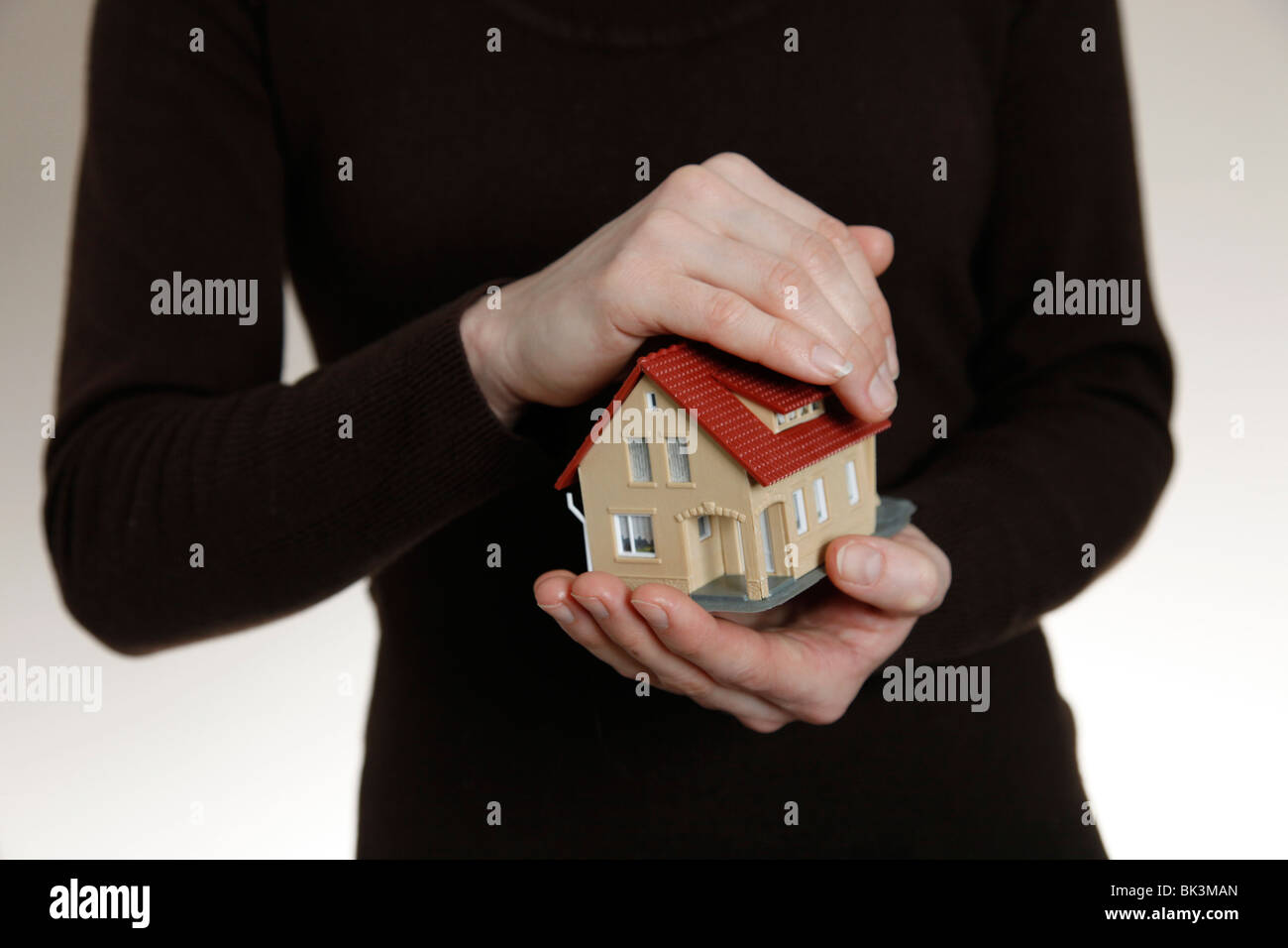 Hands holding a model house. Symbol: Property as a save investment - Stock Image
