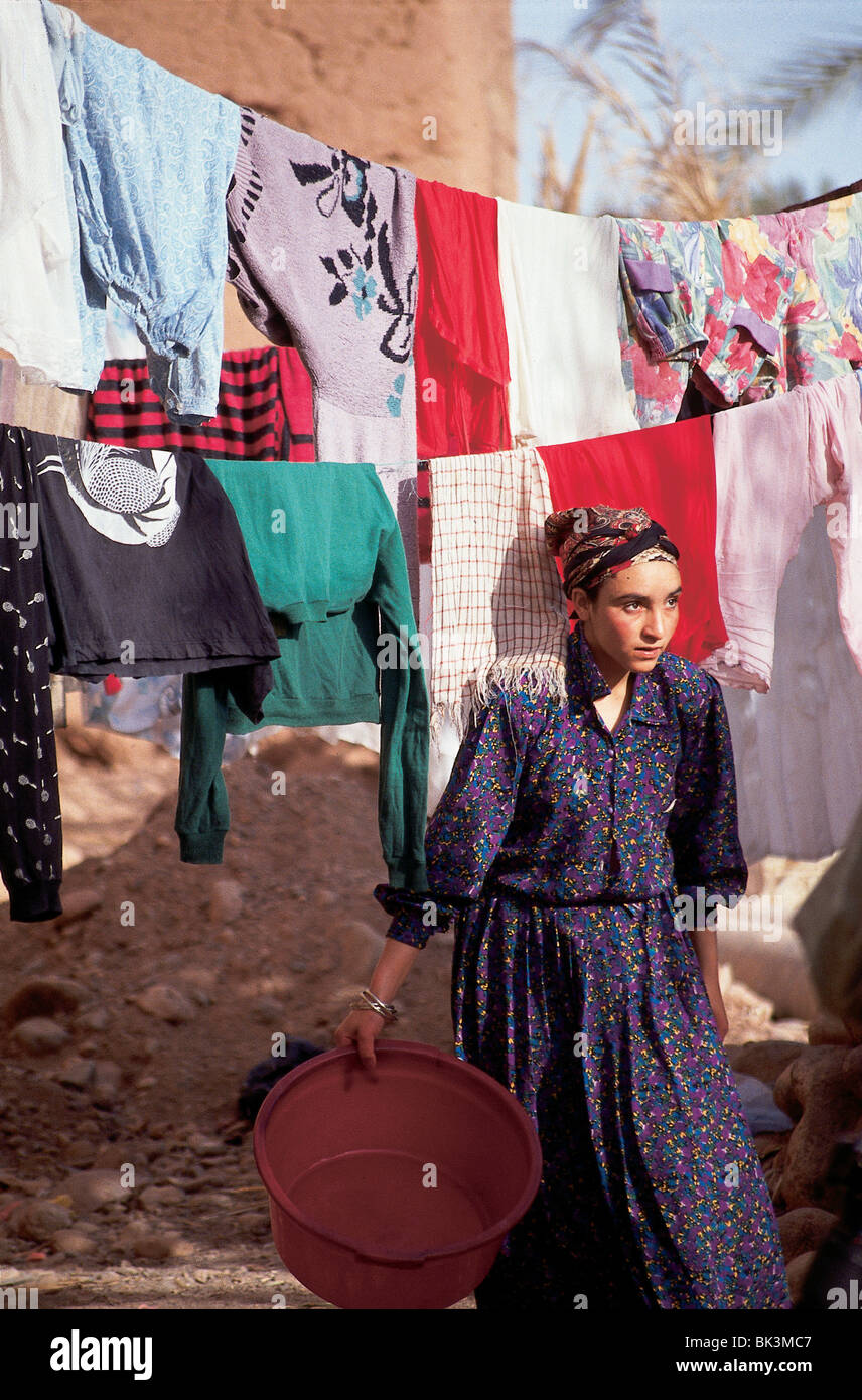 Woman with drying laundry on a clothesline, Morocco - Stock Image