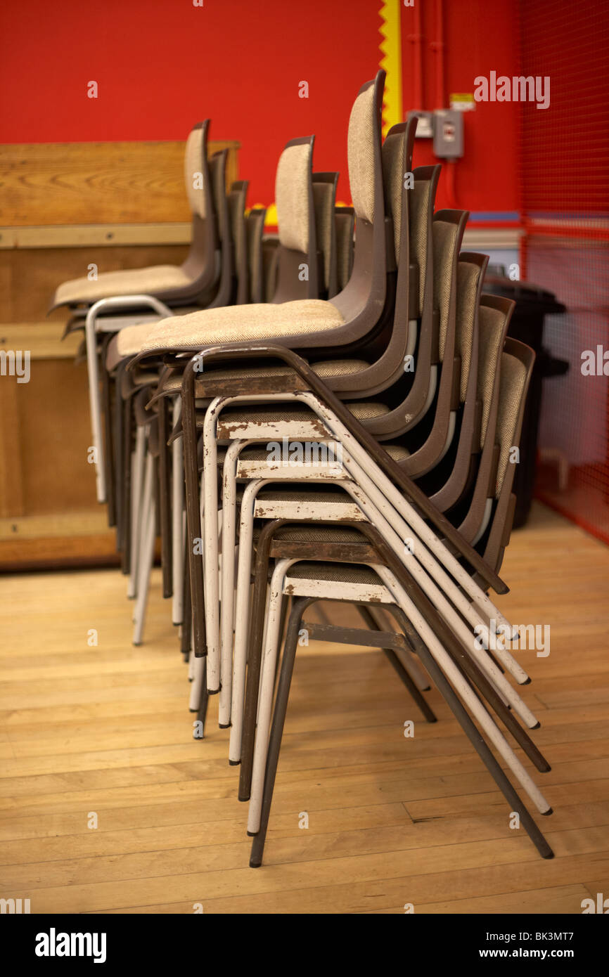 piles of stacking chairs unused in a classroom in the uk - Stock Image
