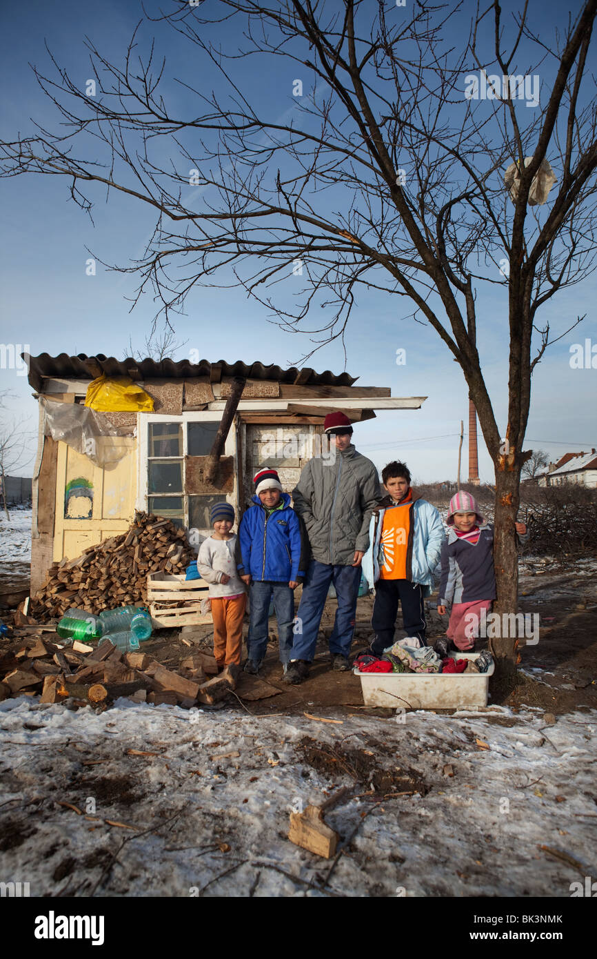 A Roma family outside the shack they share together with their parents on the outskirts of Arad - Stock Image