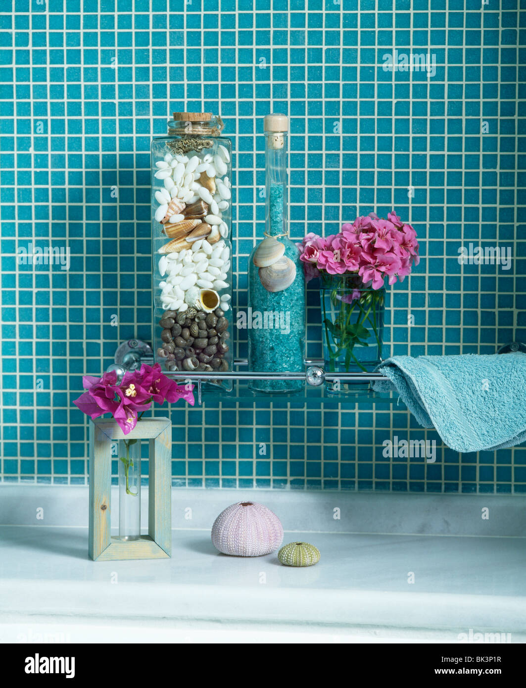 Turquoise tiled wall above shelf with tall glass jars of pebbles and ...