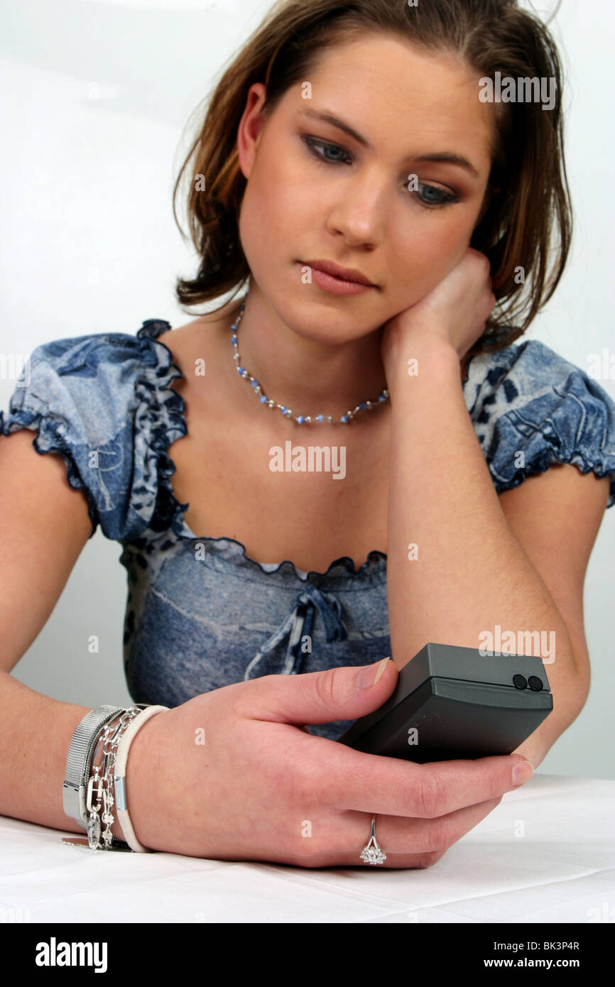Young woman looking worried at telephone display - Stock Image