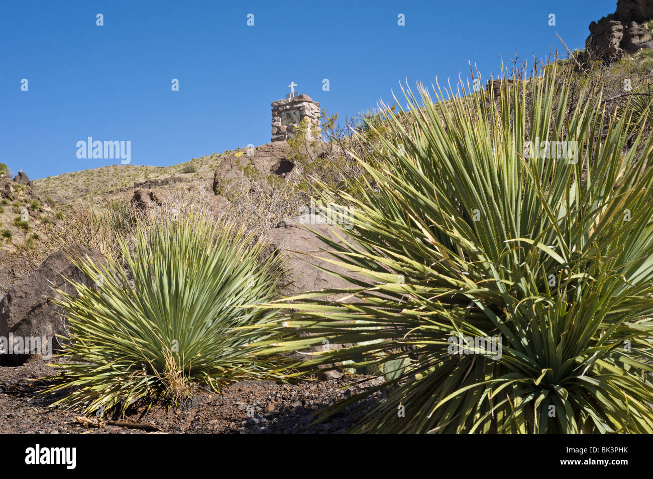 Under a blue sky stands one of the stone Stations of the Cross, Santo Nino de Atocha church, Three Rivers, New Mexico. - Stock Image