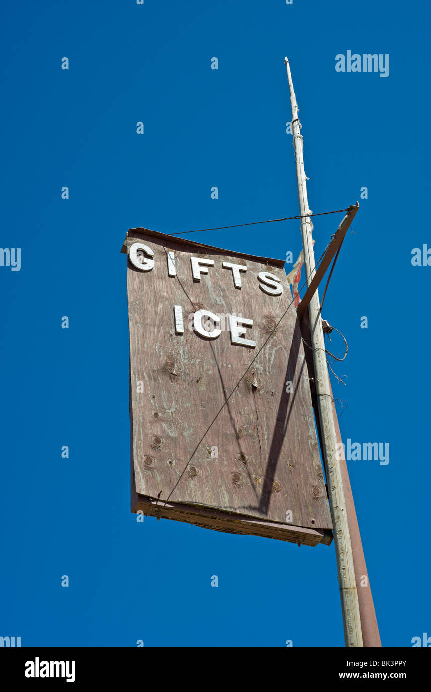 An old wood sign for gifts and ice fades in the intense desert sun at Three Rivers Trading Post, New Mexico. - Stock Image