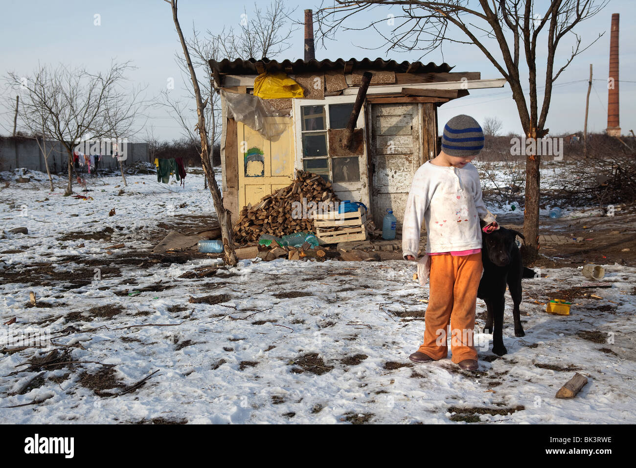 A young girl outside the small hut she shares with her family in a Roma community within Arad, Romania. - Stock Image