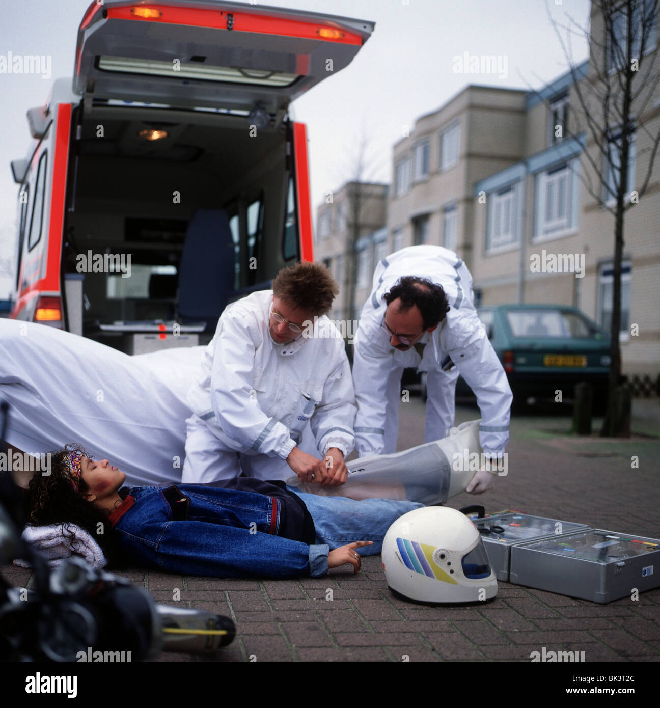 Ambulance and paramedics taking care of teenage girl after accident Stock Photo